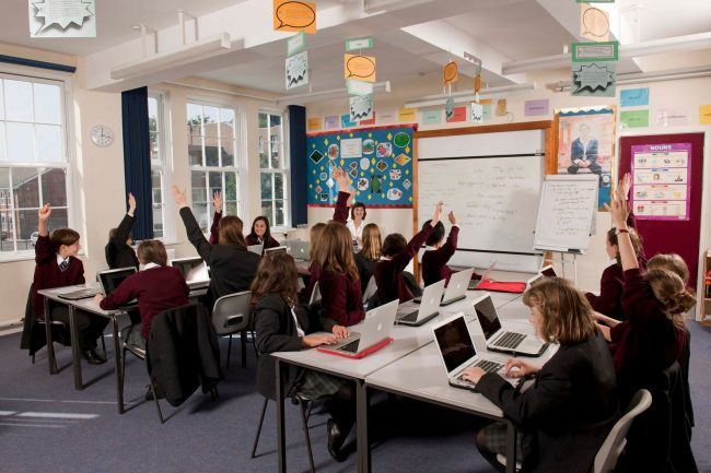 British and international high school exchange students working from laptops in a British private boarding school in England