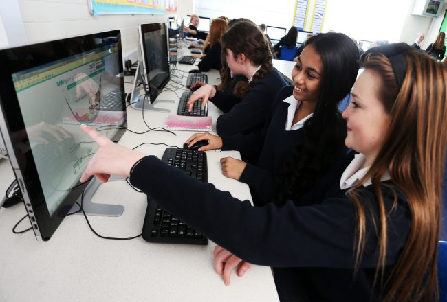 British student and exchange student working together on a computer