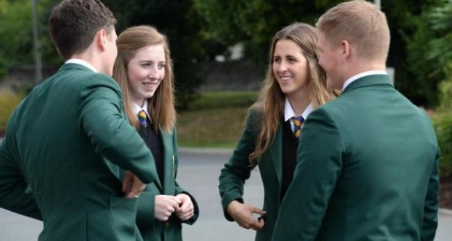 Girls and boys chatting at break time in a high school in Ireland