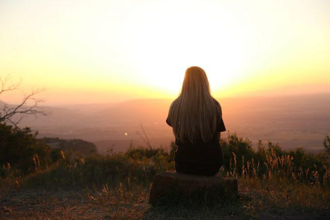 girl alone watching sunset